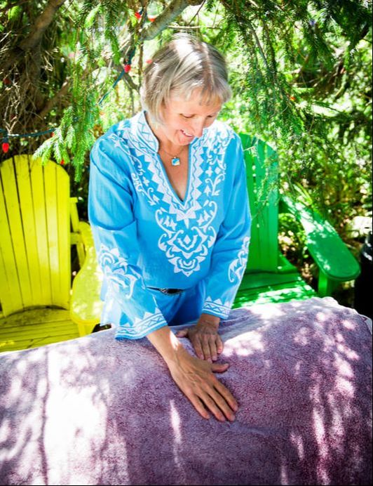 Joan doing Reiki on a client outside in her beautiful garden
